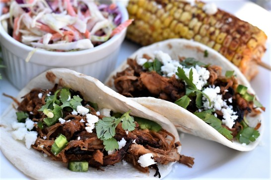 Crock pot pork carnitas tacos with grilled Mexican corn and coleslaw.